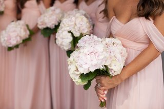 bridesmaids-in-pink-dresses-carrying-bouquets-of-white-and-pink-flowers