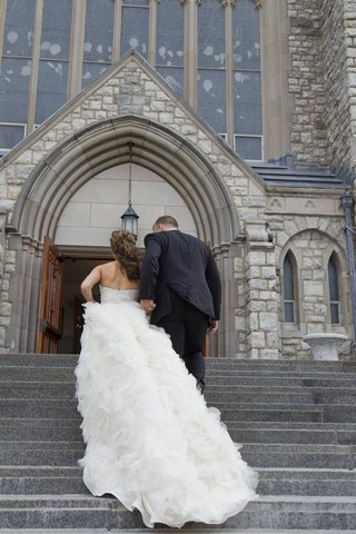 bride-in-a-strapless-lazaro-dress-with-ruffly-cathedral-train-groom-in-black-tuxedo-at-st-teresa