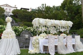 opulent-wedding-cake-next-to-glamorous-reception-table