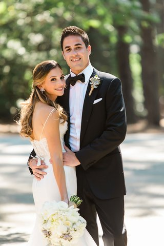 bride-in-lace-sleek-wedding-dress-long-hair-earrings-bouquet-groom-in-bow-tie-and-rustic-boutonniere