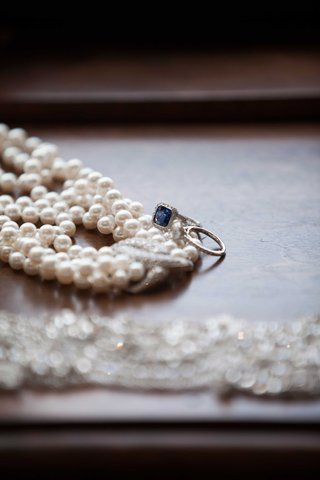 a-pearl-necklace-on-a-wooden-surface-next-to-two-lovely-rings