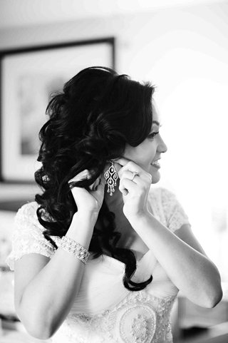 black-and-white-photo-of-bride-putting-on-earrings
