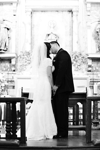black-and-white-photo-of-couple-kissing-at-altar