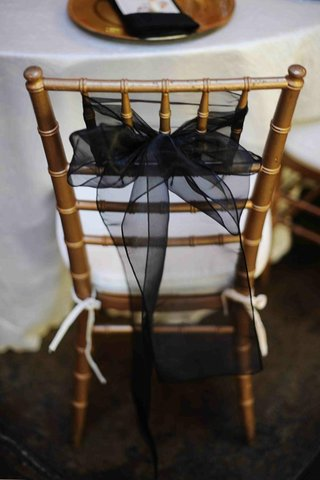 gold-chair-with-white-cushion-and-black-ribbon-decoration