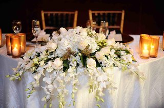 cascading-flowers-over-edge-of-white-covered-table
