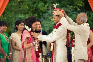 indian-bride-and-groom-exchange-garlands-of-red-and-white-roses-during-ceremony