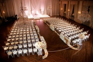 wood-floor-ballroom-white-drapery-white-ceremony-chairs-flower-petals-and-walls-along-aisle-ribbon