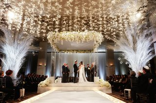 bride-and-groom-standing-under-chuppah-white-decor-butterfly-lucite-column