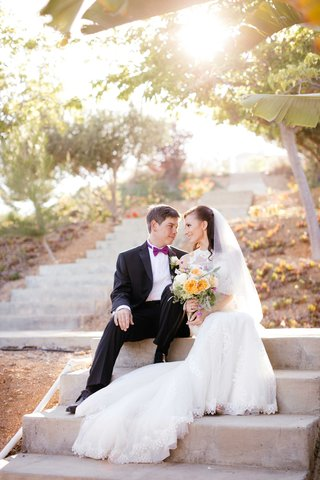 bride-and-groom-sit-on-steps-of-venue-and-look-at-each-other