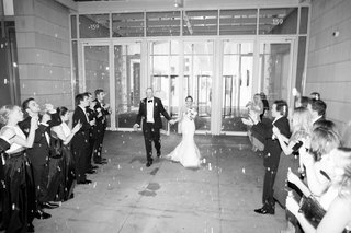 black-and-white-photo-of-bride-and-groom-make-grand-exit-as-guests-blow-bubbles