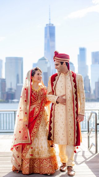 bride-in-red-and-gold-traditional-wedding-attire-for-indian-ceremony-groom-with-view-of-new-york
