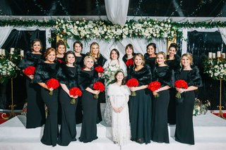 bride-with-bridesmaids-in-black-dresses-fur-wraps-bright-red-bouquet-flower-girl-in-long-sleeves