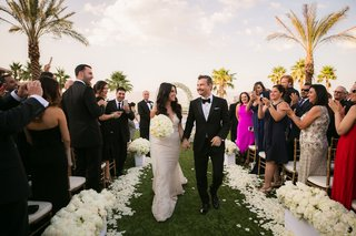 bride-in-galia-lahav-wedding-dress-holding-grooms-hand-and-bouquet-while-walking-down-grass-aisle