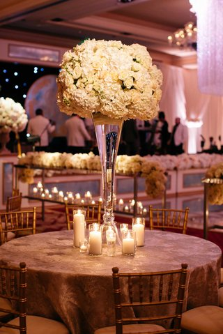 round-wedding-reception-table-with-tall-ivory-flower-arrangement-and-candle-grouping-at-base