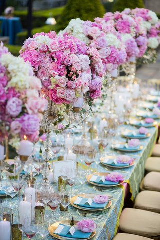 long-banquet-table-topped-with-pink-floral-arrangements