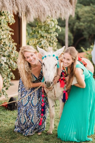 wedding-in-mexico-destination-event-rehearsal-dinner-welcome-party-guests-posing-with-donkey-in-poms