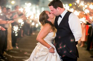 bride-in-allure-ball-gown-groom-in-navy-joseph-abboud-suit-kiss-during-sparkler-exit