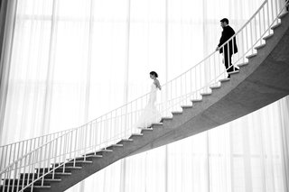 black-and-white-photo-of-bride-and-groom-walking-down-winding-staircase-at-chicago-history-museum