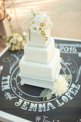 tim-lopez-and-jenna-reeves-wedding-cake-rustic-reception-white-square-tiers-fresh-flowers