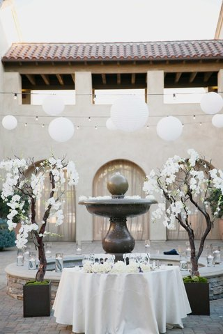 sweetheart-table-in-front-of-fountain-during-daylight-white-flowers-on-trees-and-lanterns
