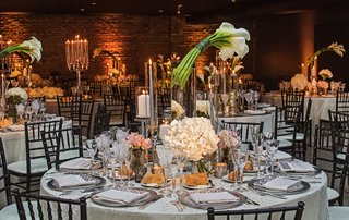 wedding-reception-brick-wall-round-table-calla-lily-flower-centerpiece-glass-hurricane-hydrangea