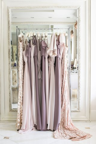 bridesmaid-dresses-in-shades-of-light-purple-on-clothing-rack-in-front-of-mirror-bridal-suite