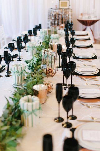 a-unique-reception-tablescape-with-black-glassware-copper-chargers-and-utensils-and-a-green-runner