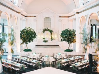 wedding-reception-vibiana-long-round-tables-trees-altar-decorated-with-greenery-pillars-centerpieces