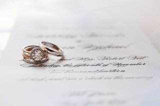 engagement-ring-and-wedding-bands-sit-atop-the-couples-wedding-invitation