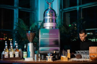 server-behind-coffee-and-espresso-station-at-wedding-reception-night-time