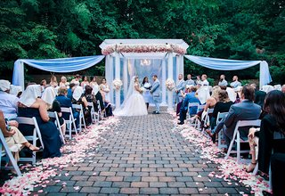 wedding-ceremony-courtyard-brick-aisle-white-pink-flower-petals-drapery-arch-arbor-pink-flowers
