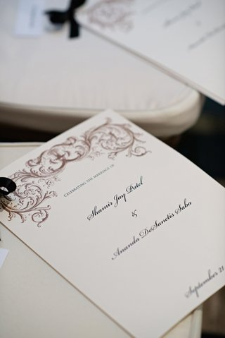 ceremony-booklet-tied-with-black-ribbon-on-chair