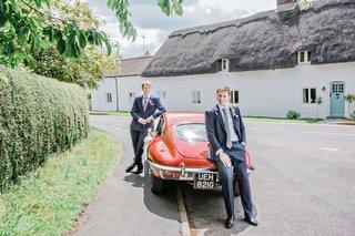 red-vintage-car-english-british-groom-groomsman-transportation-blue-suits-tuxedos-england-uk-wedding