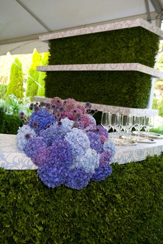 a-colorful-arrangement-of-blue-and-purple-hydrangeas-on-bar-with-white-and-blue-counter-and-greenery