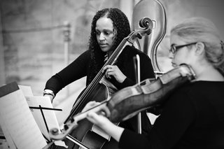 black-and-white-photo-of-a-cellist-and-violinist-from-the-chicago-sinfonietta-at-wedding-ceremony
