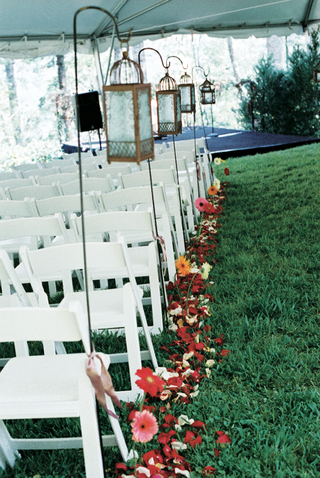 outdoor-ceremony-with-white-chairs-and-lanterns