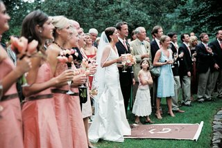 wedding-party-and-guests-participate-in-champagne-toast-in-garden