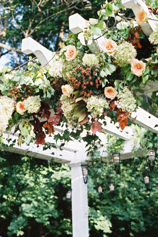 white-garden-ceremony-structure-with-orange-roses-and-white-flowers