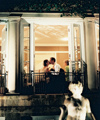 bride-and-groom-kiss-at-reception-through-window-view