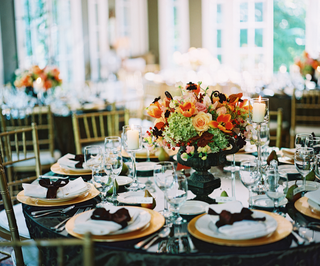 table-with-gold-chargers-and-black-urn-filled-with-orange-green-and-pink-flowers