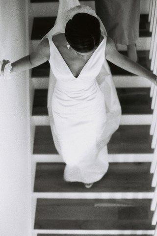 black-and-white-picture-of-bride-walking-down-staircase-wearing-v-neck-wedding-dress