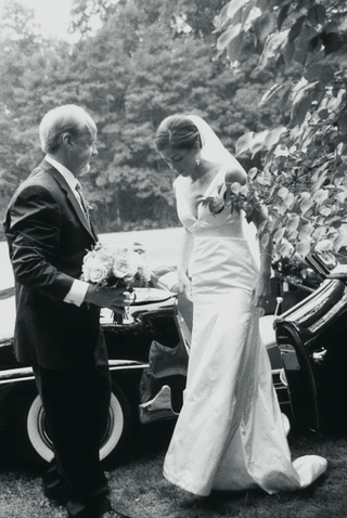 black-and-white-photo-of-bride-getting-out-of-classic-mercedes-wedding-car
