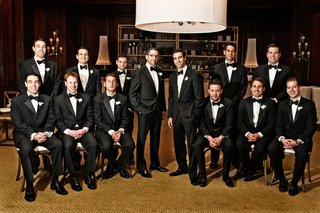 groom-with-12-groomsmen-in-black-tuxedos-and-bow-ties