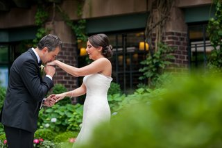 groom-kisses-brides-hand-first-look-wedding-washington-dc-four-seasons-tuxedo-dress