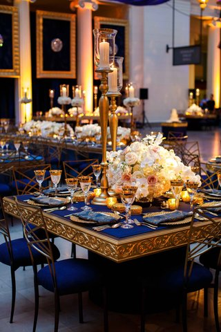 blue-and-gold-tablescapes-with-tall-gold-candles-and-low-white-floral-arrangements