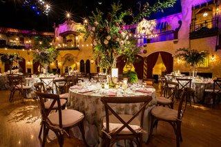 wedding-reception-round-table-flower-print-linen-vineyard-wood-chair-tall-centerpiece-greenery-roses