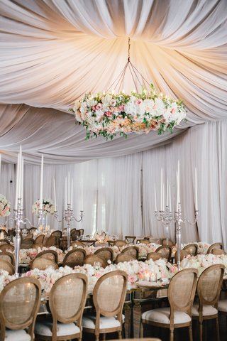 drapery-at-wedding-reception-with-large-floral-chandelier-over-guest-tables-long-mirror-tables