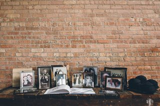 wedding-ceremony-rustic-brick-wall-with-family-photos-in-frames-and-guest-book-on-table