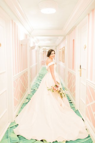 the-confused-millennial-v-back-off-shoulder-blush-ball-gown-wedding-dress-the-colony-hotel-hallway