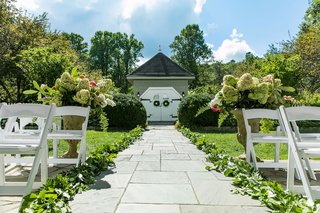 wedding-ceremony-outdoor-old-edwards-inn-stone-aisle-greenery-white-chairs-urn-with-colorful-flowers